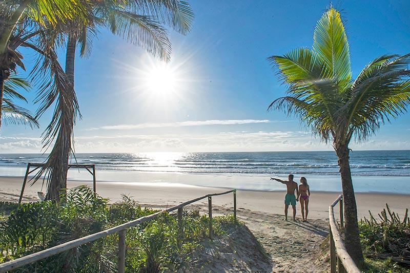 Casal em frente mar onde o resort oferece toda estrutura com cadeiras e gazebo