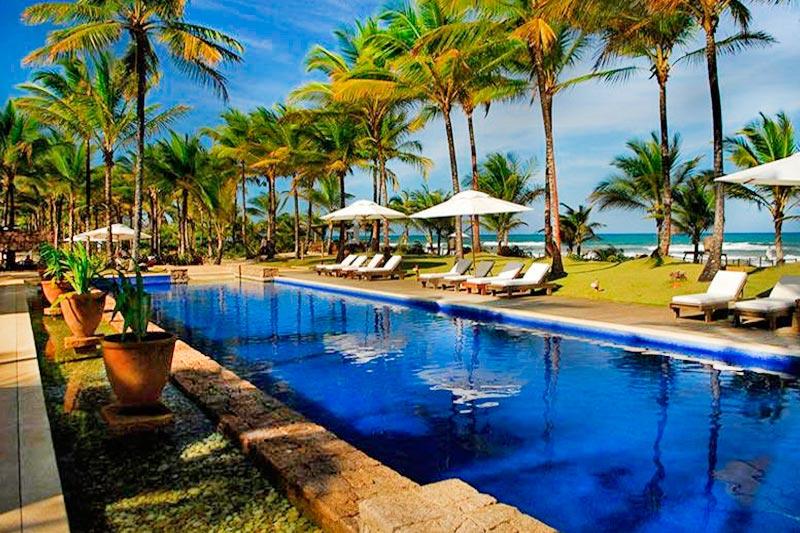 Vista diagonal piscina com os gazebos postos junto as cadeiras e em frente ao mar lindíssimo!